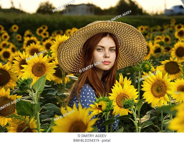 Serious Caucasian woman wearing hat in field of sunflowers