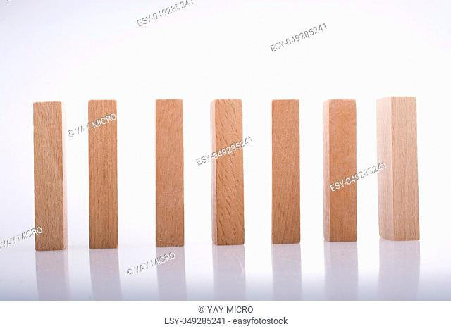 Wooden Domino Blocks in a line on a white background