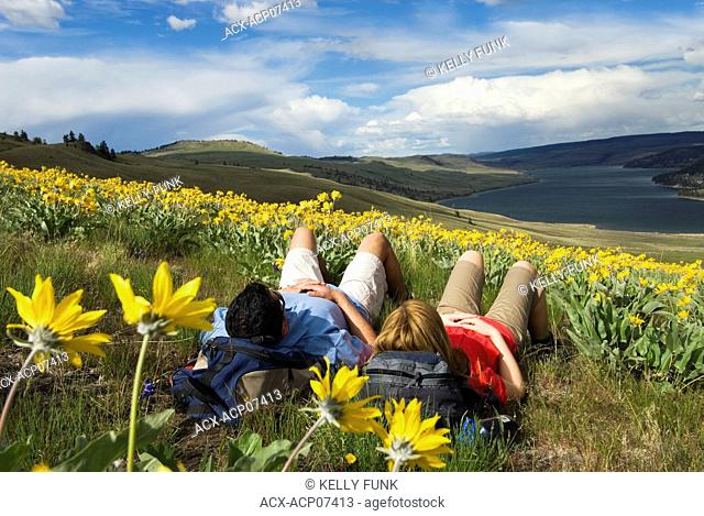 A young couple takes a break from hiking in the wildflowers above Stump Lake, just South of Kamloops, British Columbia, Canada