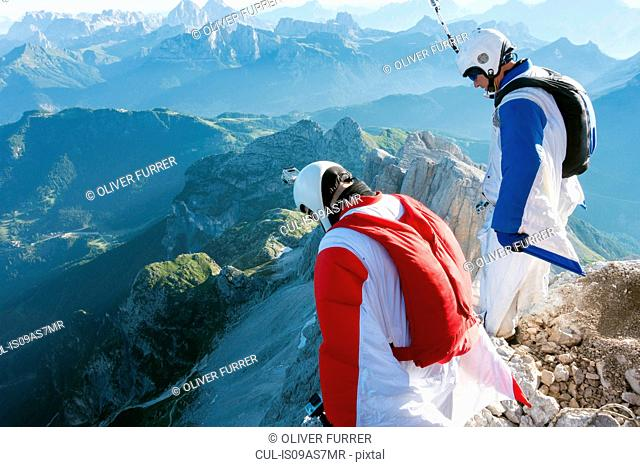Two male BASE jumpers standing on edge of mountain looking down, Dolomites, Italy