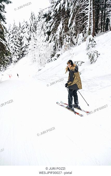 Portrait of happy young woman skiing in winter forest