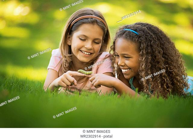 Two girls lying on the grass, one holding a green caterpillar on her finger