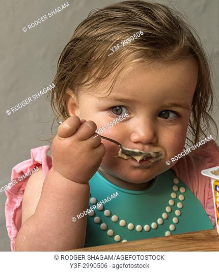 two-year old learning to feed herself from the bowl usoing a teaspoon. Cape Town, South Africa