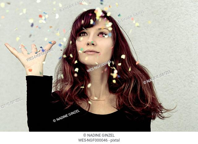 Young woman looking at confetti in the air