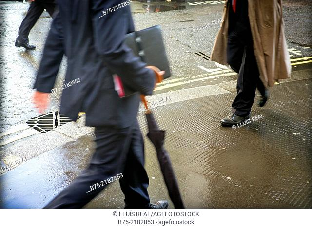 Unrecognizable businessmen with portfolio and umbrella walking down in the street in the city of London, England, UK