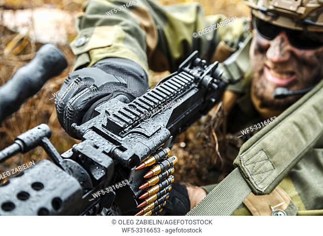 Norwegian Rapid reaction special forces FSK soldier reloading weapon. Field camo uniforms, combat helmet and eye-wear goggles are on