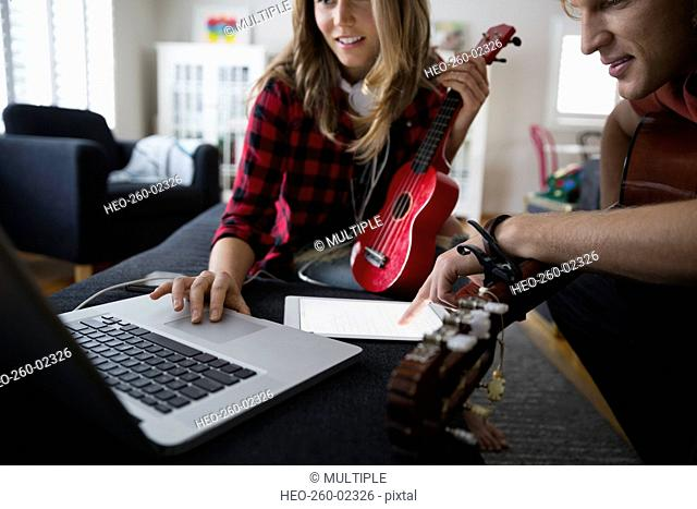 Couple with guitar and ukulele using laptop