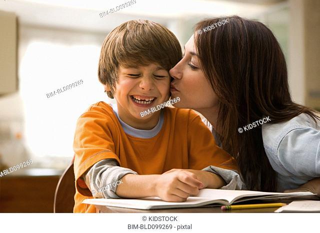 Caucasian mother kissing son