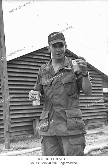 A United States Army serviceman in his uniform, he is carrying a can of Pepsi in one hand and a paper cup in the other, one of the wooden buildings on base can...