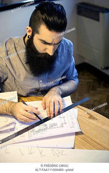 Architect working with blueprints in office