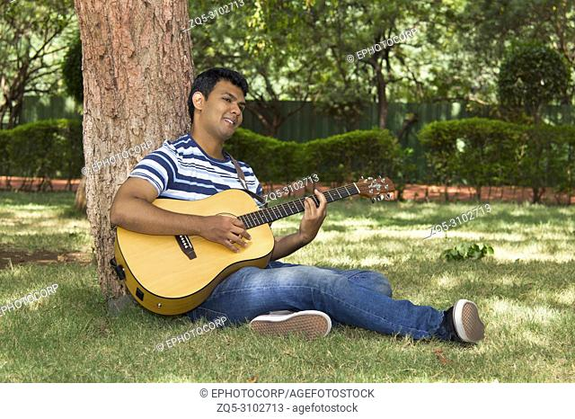 Young man playing guitar under tree