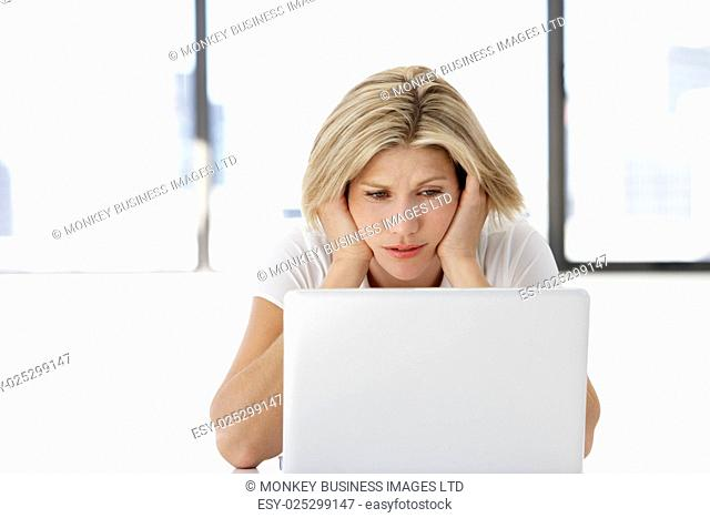 Frustrated Businesswoman Sitting At Desk In Office Using Laptop