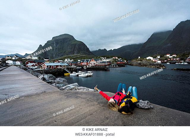 Norway, Lofoten, two young women lying on a pier at the coast taking a selfie