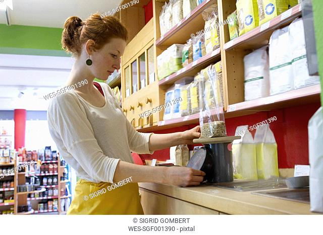 Young woman in wholefood shop weighing granola