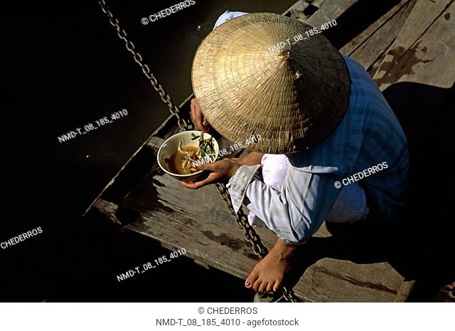 High angle view of a man eating food and sitting in a boat, Vietnam