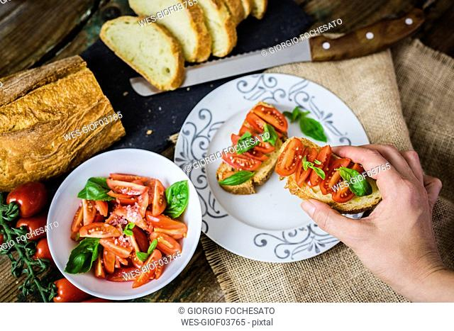 Taking bruschetta, white bread with tomato and olive oil