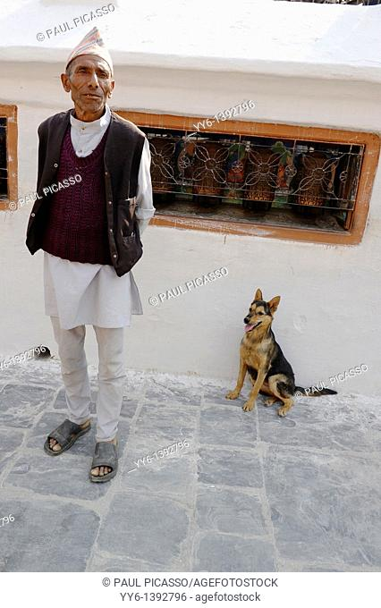 nepalese man and his dog, boudhanath , one of the holiest Buddhist sites in Kathmandu , Nepal