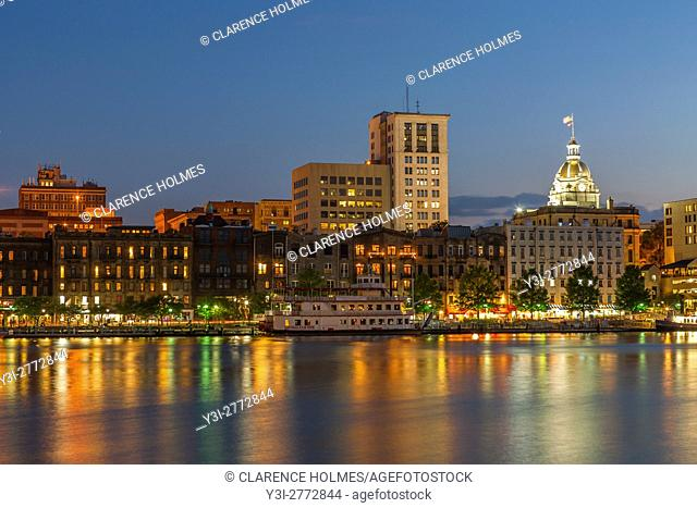 The lights of River Street and the skyline are reflected in the Savannah River at twilight in Savannah, Georgia