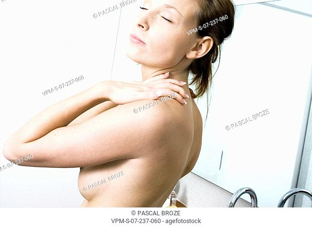 Side profile of a naked young woman massaging her shoulders with massage oil