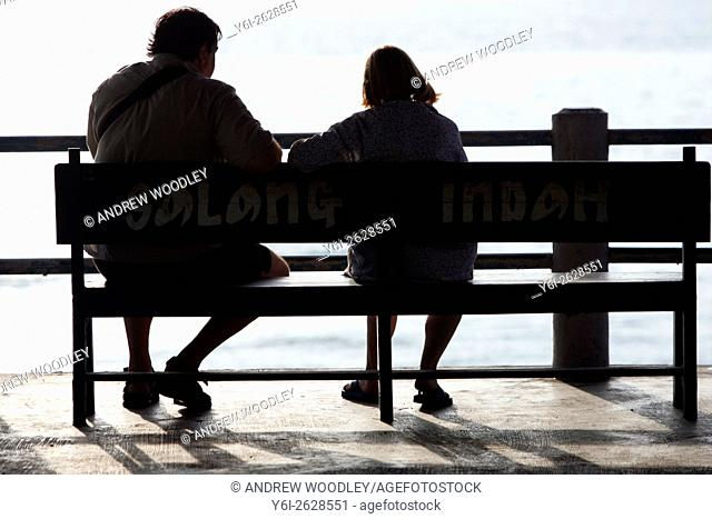 Couple sit at end of pier Salang Beach Tioman Island Malaysia
