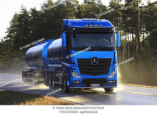 Salo, Finland - November 24, 2018: Blue Mercedes-Benz Actros tank truck of Kuljetusliike Markus Hanninen Oy moves on wet highway on sunny autumn day