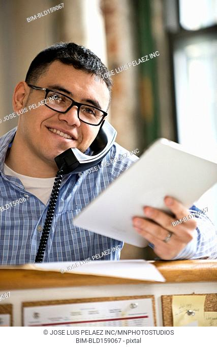 Hispanic businessman with digital tablet talking on telephone