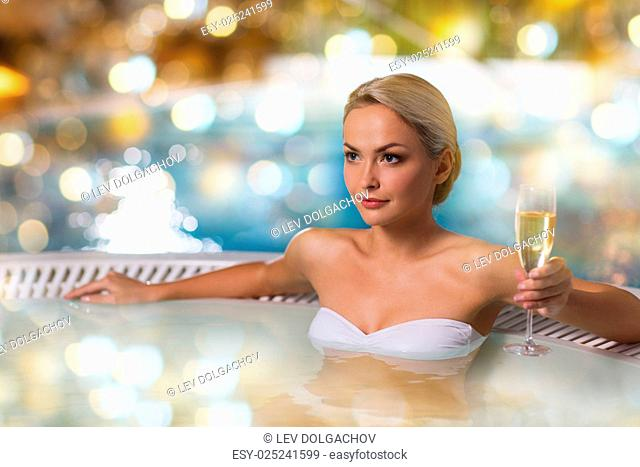 people, beauty, spa and relaxation concept - beautiful young woman wearing bikini swimsuit sitting with glass of champagne in jacuzzi at poolside over holidays...