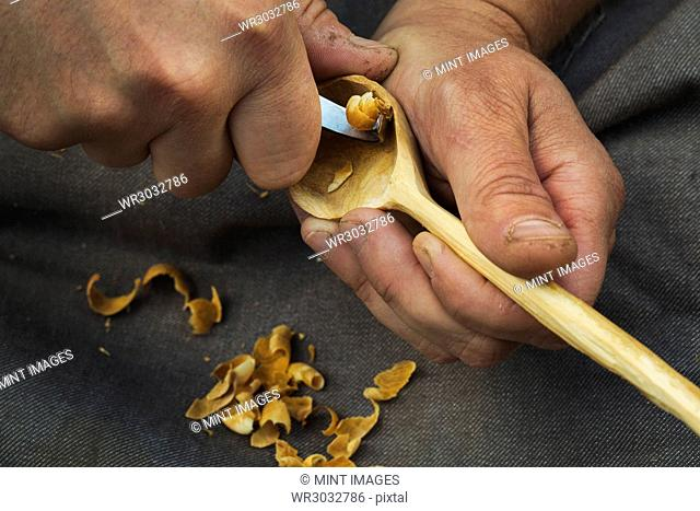 A craftsman carving wood, shaping the bowl of a handcarved wooden spoon with a sharp handheld tool