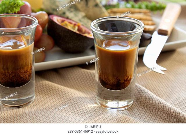 Coffee liquer with a delicious fruit and cheese platter featuring different cheeses and fresh fruits