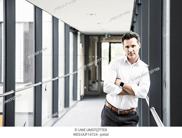 Portrait of confident businessman in office passageway