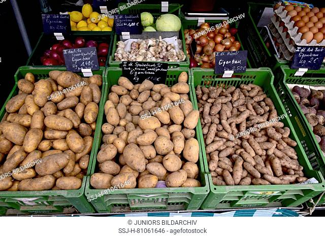 Market stall offering different sorts of potatos, garlic and onions