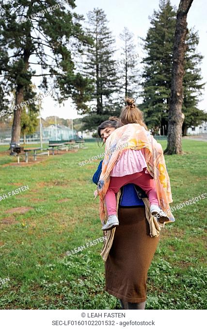Mother carrying daughter (4-5) in park