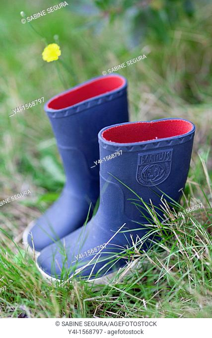 Blue rain boots of a child placed in the grass