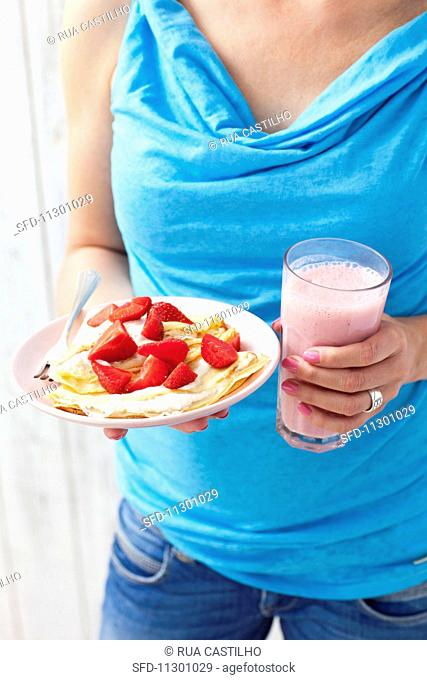 A woman holding a strawberry milkshake and pancakes with cottage cheese and strawberries