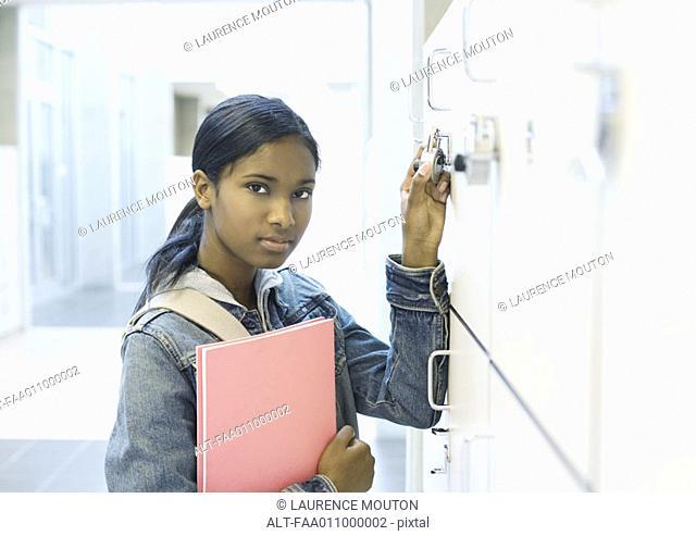 Teenage girl opening locker