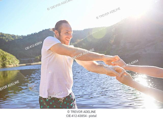 Playful couple holding hands at sunny summer lake