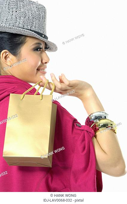 Woman carrying a shopping bag and smiling