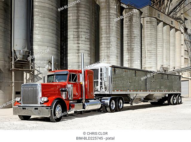 Semi-truck at industrial silos