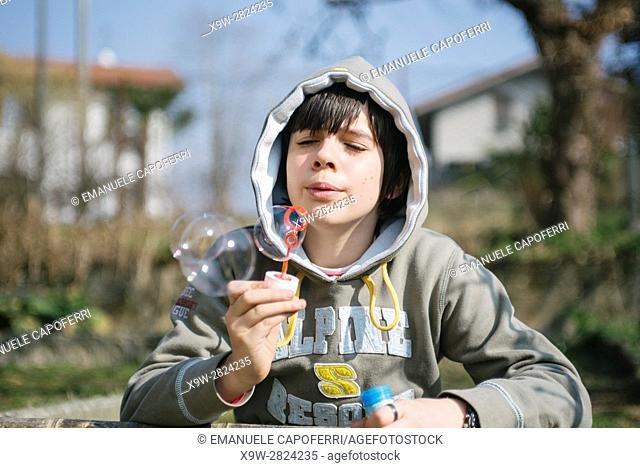 boy makes soap bubbles, malgesso.italy