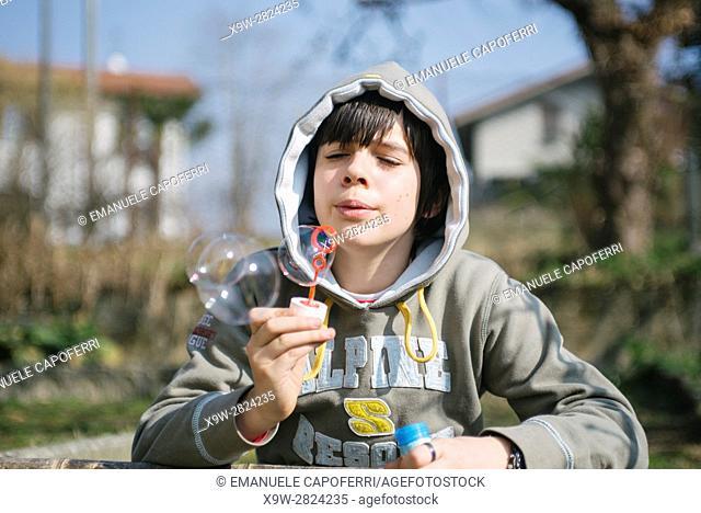 boy makes soap bubbles, malgesso.italy