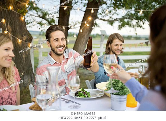 Group of friends toasting at farm dinner party