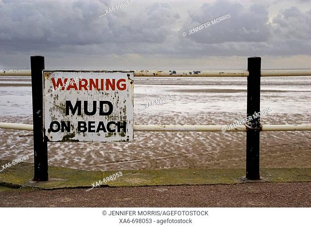 An aged and rusting sign attached to a promenade railing warns of mud on the beach. A cold winter sky reflects on the wet sand