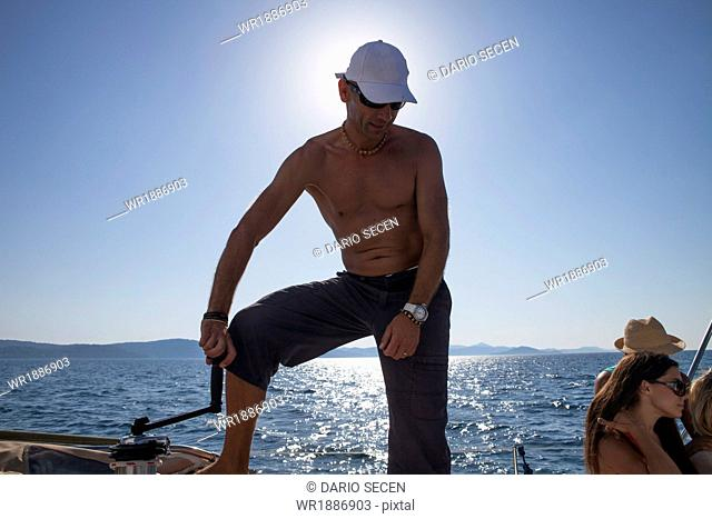 Croatia, Adriatic Sea, Young man on sailboat, people in background