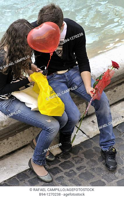 Couple in love with red balloon in the shape of heart and a red rose. Trevi Fountain. Rome, Italy
