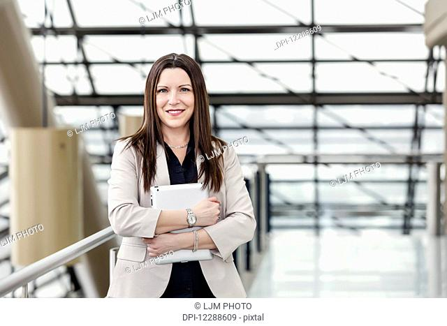 Mature business woman posing in an atrium and holding a tablet; Edmonton, Alberta, Canada