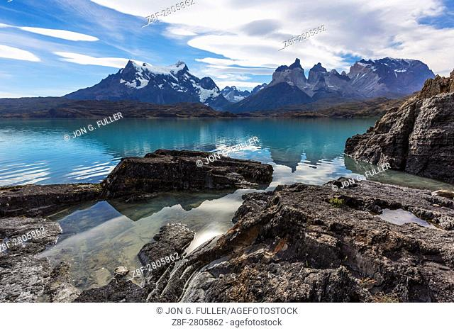 """Wide-angle view of the Paine Masif with rocks and Lake Pehoe in the foreground. From left to right â. """" Cerro Paine Grande, the Cuernos del Paine, or the Horns"""