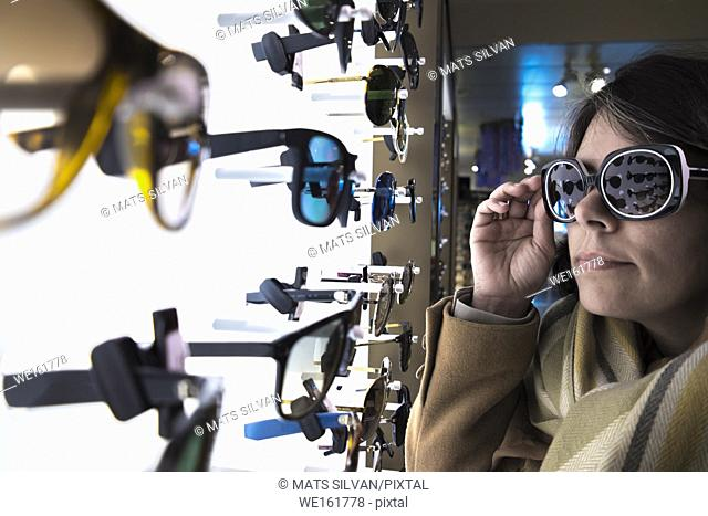 Woman Testing Sunglasses in Retail Store