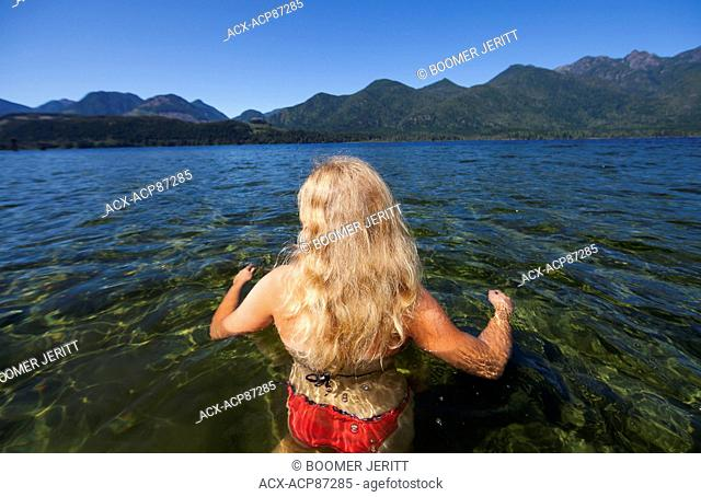 A young girl takes to the warm waters of Nimpkish Lake