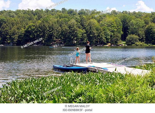 Two young girls standing on jetty, fishing using fishing rods