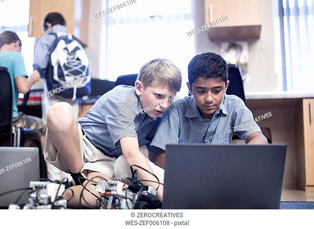 Schoolboys with laptop in robotics class
